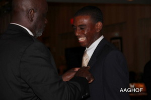 Jimmy Garvin, Chair of the Collegiate & Youth African American Hall of Fame pins Norman F. Blanco after his induction.